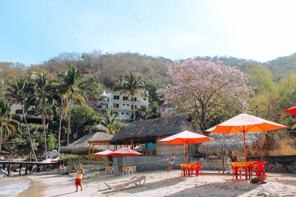 Brightly colored umbrellas on the beach at Boca de Tomatlan one of the best day trips from Puerto Vallarta