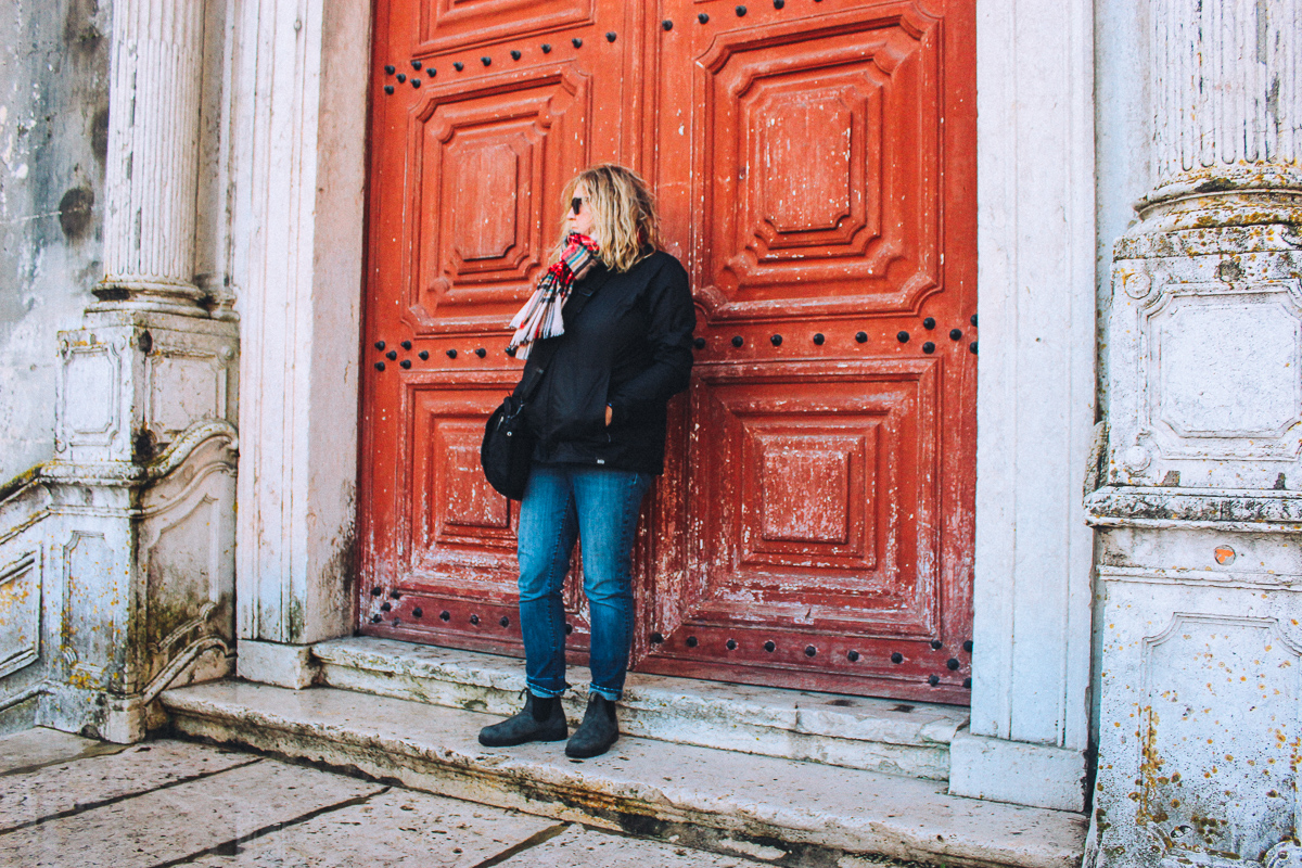 Southerner Says standing in front of some old wooden doors in Lisbon