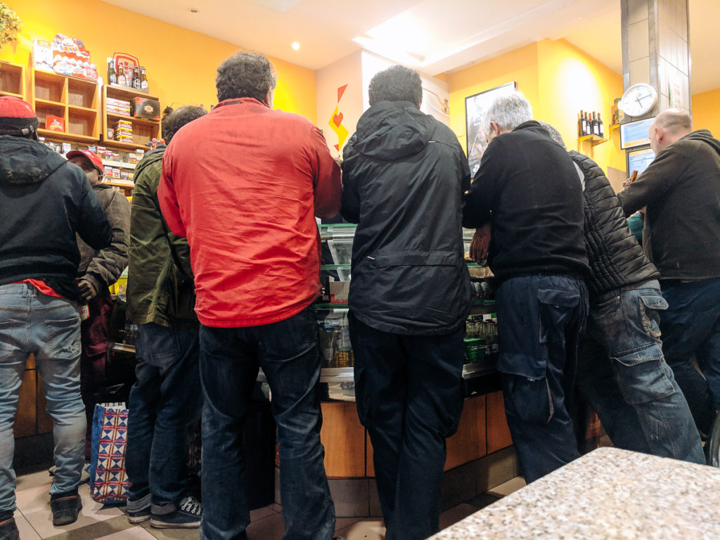 People standing around the counter the coffee shop